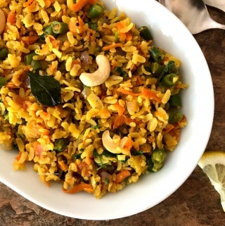 A plate with spiced poha on the table