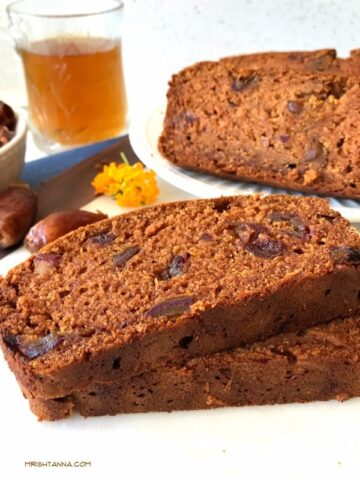 Two slices of mango bread on a plate, with dates