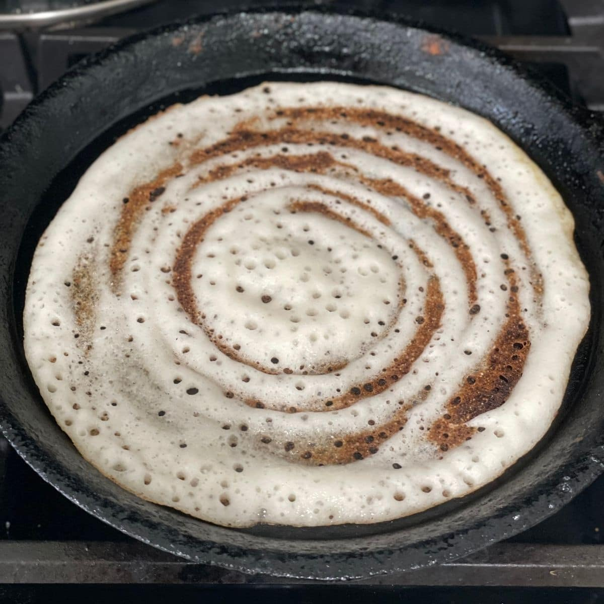 A pan is with dosa over the heat