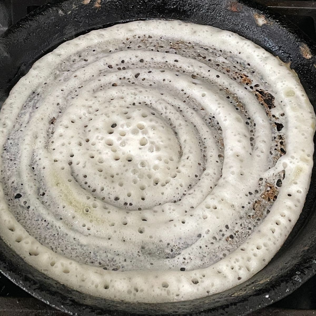 A cast iron pan is with dosa over the heat
