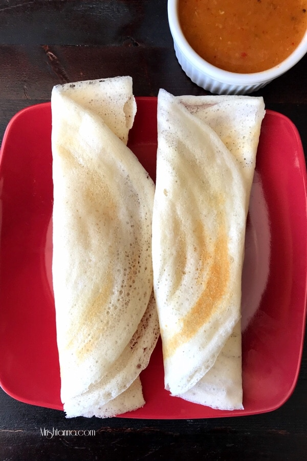 dosa is rolled and placed on the red plate