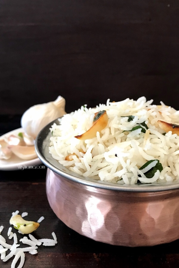 A bowl of food on a table, with garlic rice
