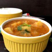 A bowl of sambar, with Onion and Potato