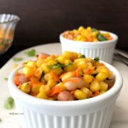 A bowl of food on a plate, with Corn salad