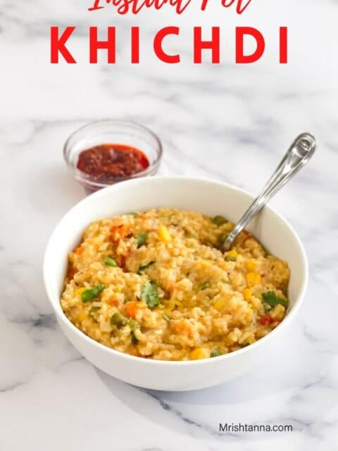 A bowl of khichdi with spoon is on the table.