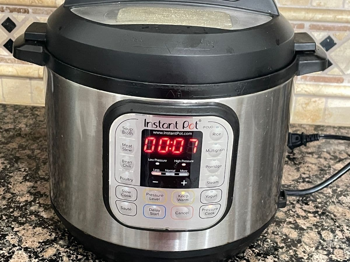 An instant pot is displaying cooking time on the counter.