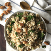 A bowl of Barley and topped with nuts