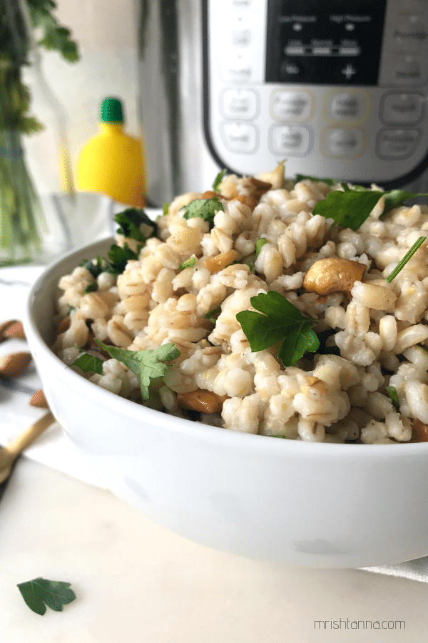 A white bowl of barley salad and topped with parsley