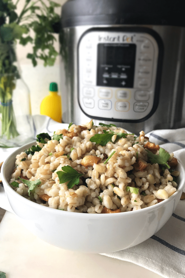 A white bowl of barley salad and topped with parsely