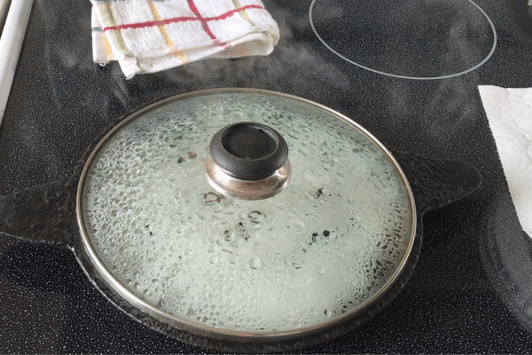 A cast iron pan is with Neer dosa over the heat