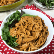 A bowl of food on a plate, with Pasta and Tomato