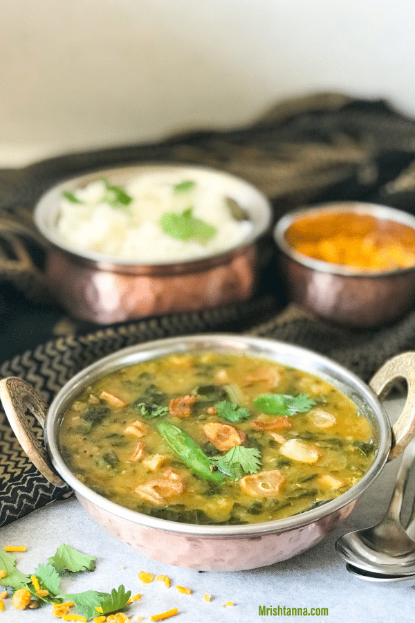 A bowl of spinach dal on the table along with rice