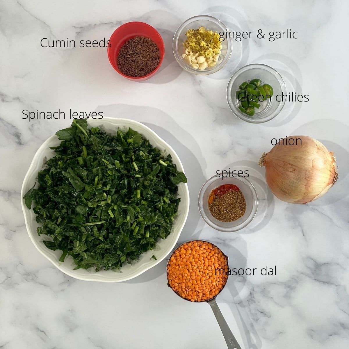 Spinach, onion, cumin seeds, and red lentils are on the table for dal recipe.