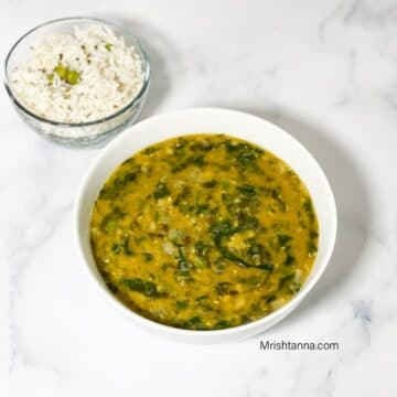 A bowl of palak dal is on the white table