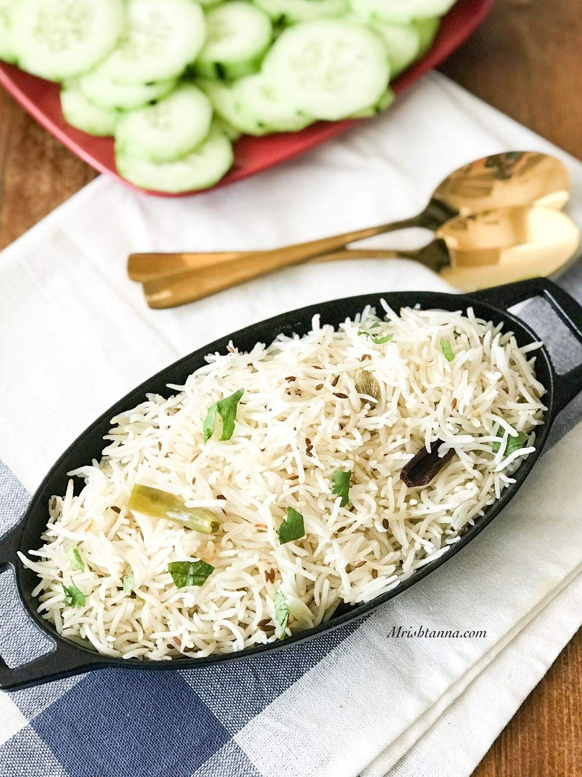 A black iron pot is filled with jeera rice and its on the table with golden spoon