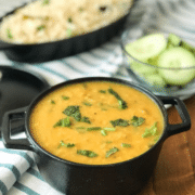 A black bowl filled with dal along with sliced cucumber