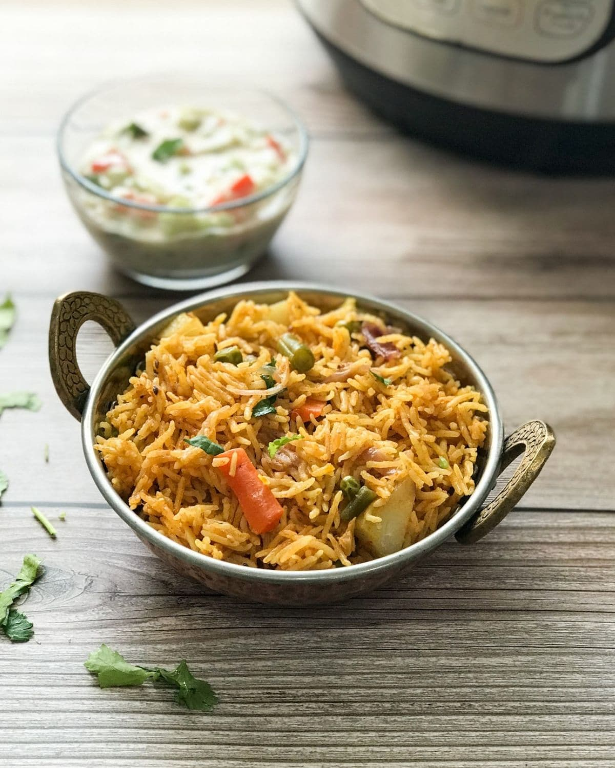 A copper bowl is with vegetable biryani over the table