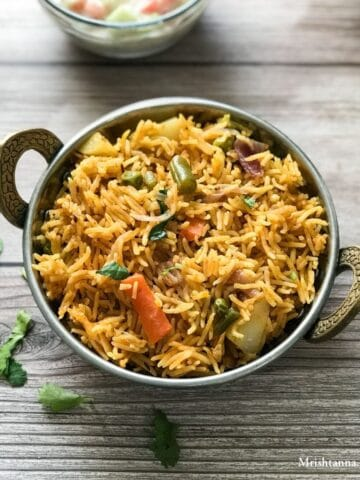 A bowl of veg biryani is on the wooden table