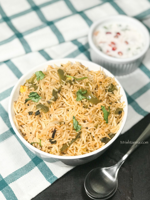 A bowl of capsicum rice on the table along with raita