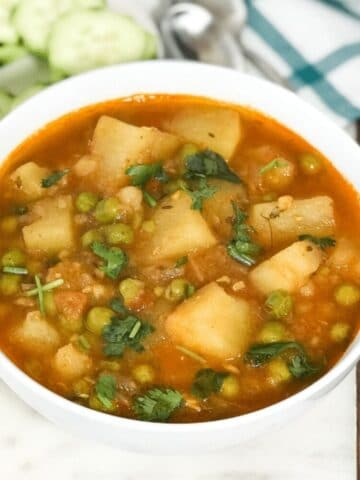 a bowl is with aloo matar curry and placed on the white serving tray