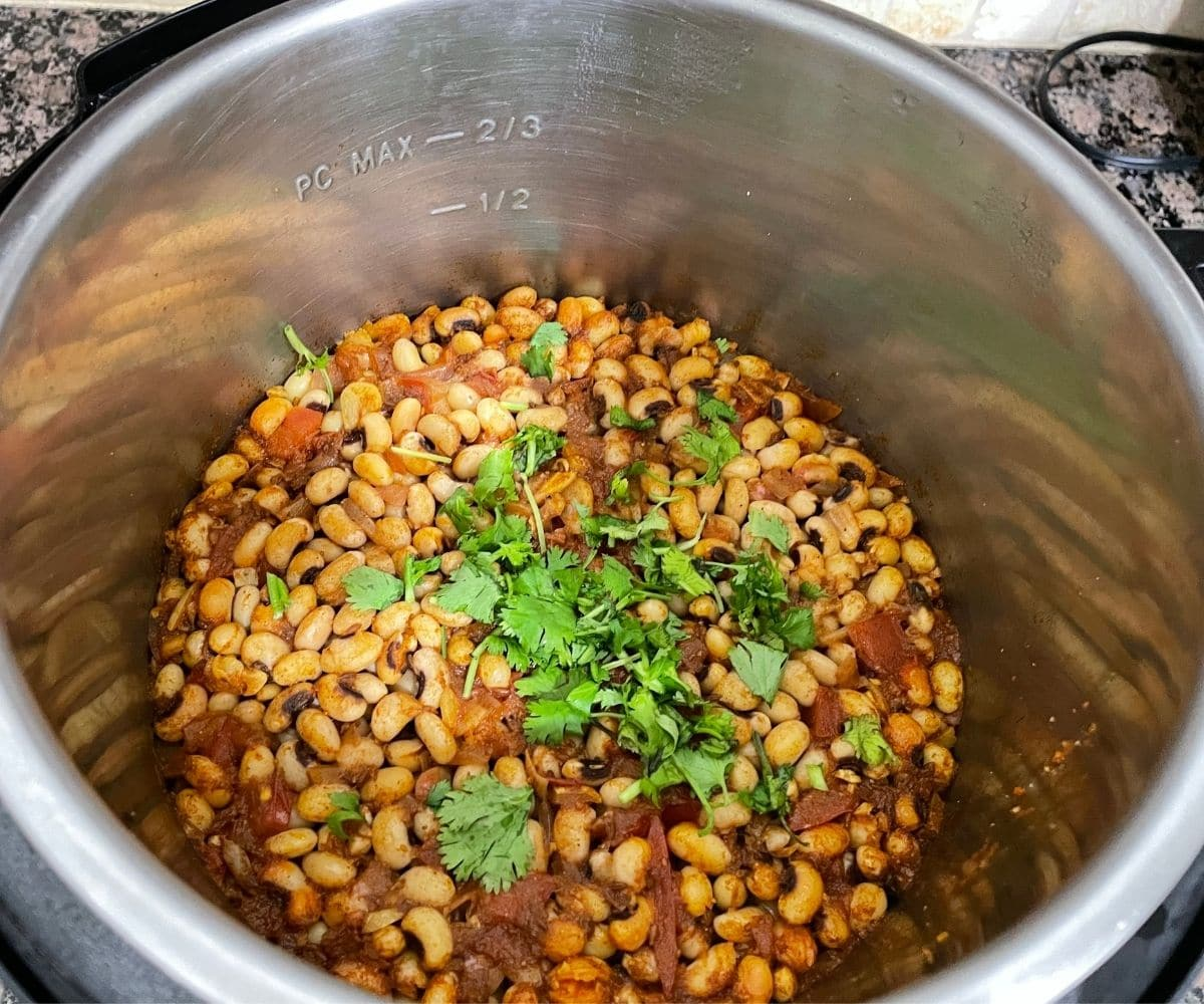 An Instant pot is filled with black eyed peas curry and topped with chopped cilantro