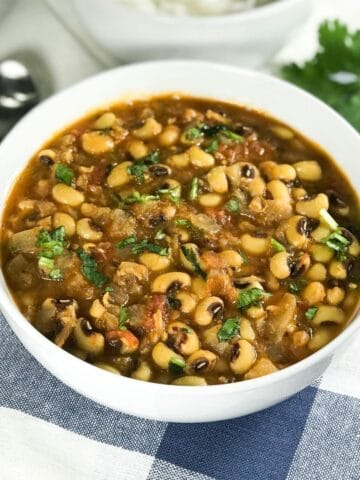 A white bowl is with black eyed peas curry along with spoons on the table
