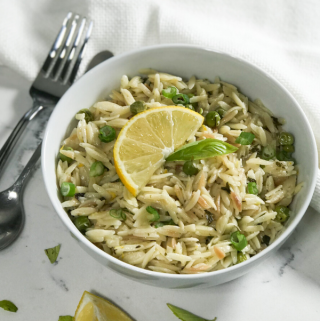 A white bowl full  lemon orzo with a side of the lemon wedge for garnish