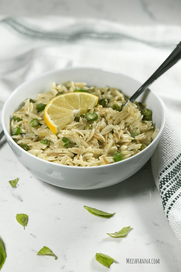 A white bowl  filled with orzo and fork inserted and a lemon wedge for garnish