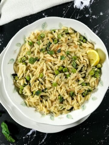 A plate of lemon orzo is on the table with lemon