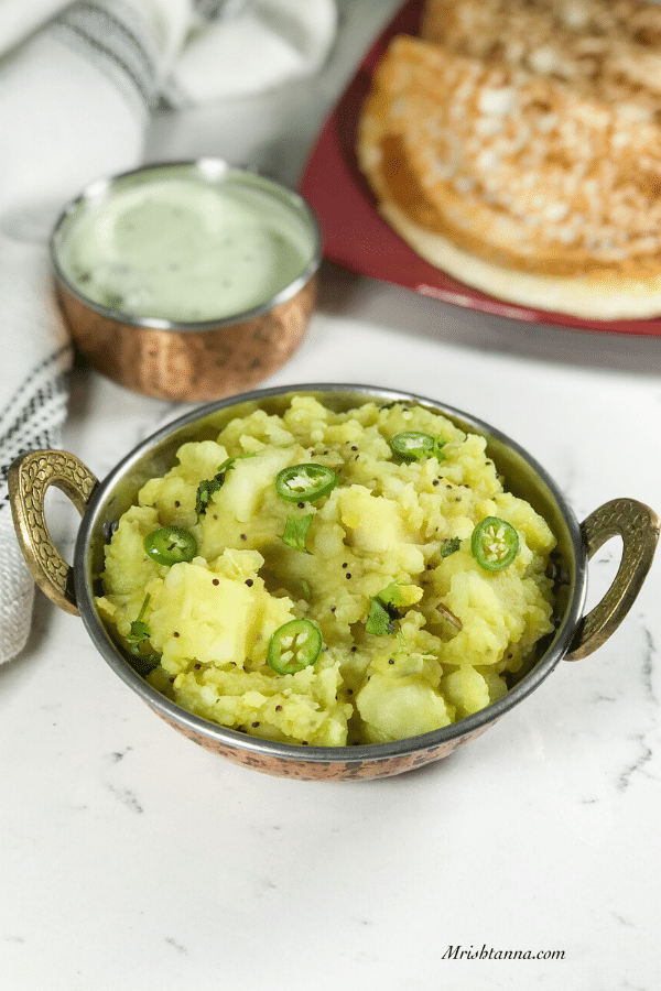 A bowl of potato masala is on the table along with dosa