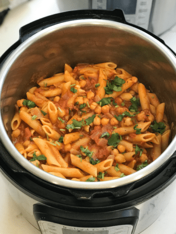 A pan filled with penne, chickpeas and vegetables