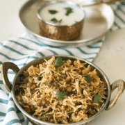 A bowl of rice on a plate, with curd