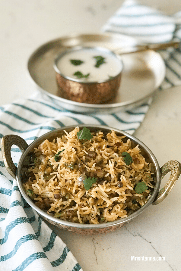 A bowl of rice on the table , with curd by the side