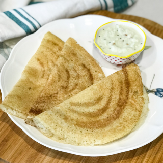 three dosas on a plate along with chutney