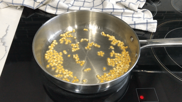A pan on the stovetop with oil and spices