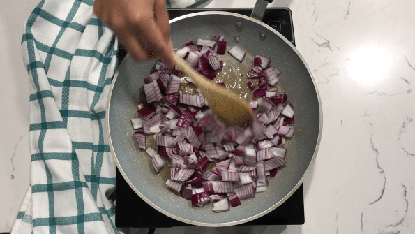 A person stirring a food, with Curry and Potato
