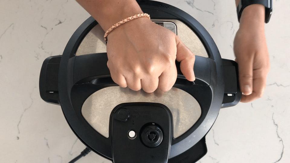 A person closing instant pot lid