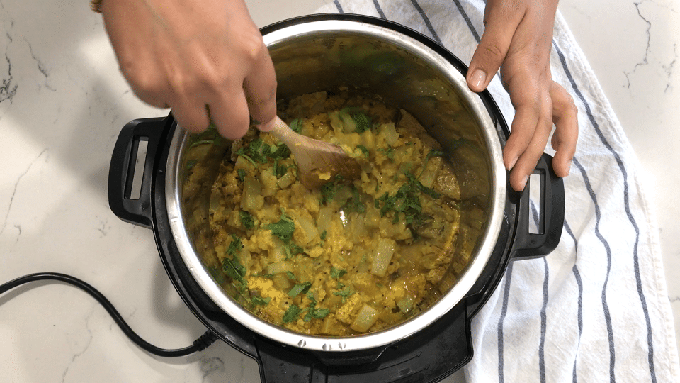 A person cooking food in a pan on a stove, with Chayote and Curry