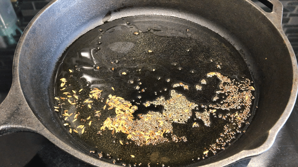 A close up of a cast iron pan on a stove, with oil and spices