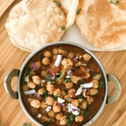 A bowl of food sitting on top of a wooden table, with Chana masala