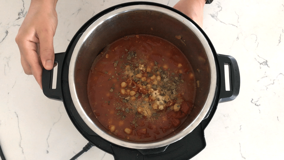 A bowl of curry on a stove, with Chana masala and Gravy
