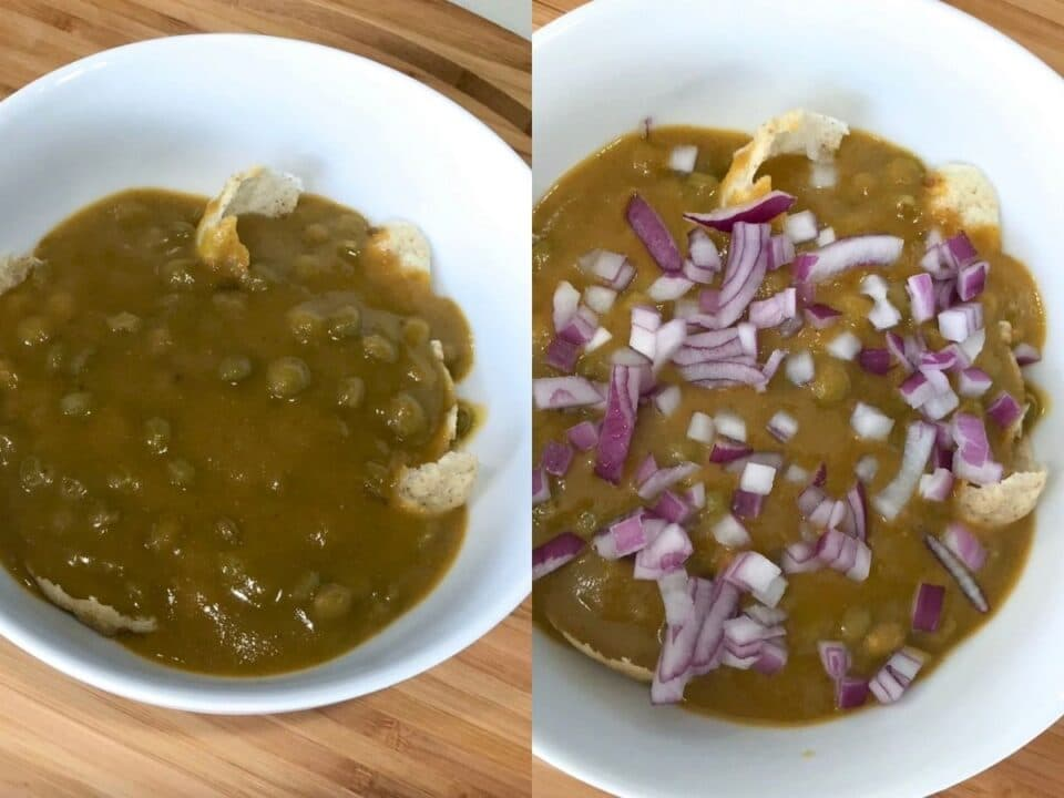 A bowl is with masala puri and topped with onions