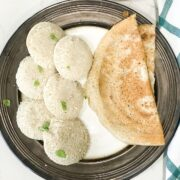 Millet idli placed on big plate with, dosa