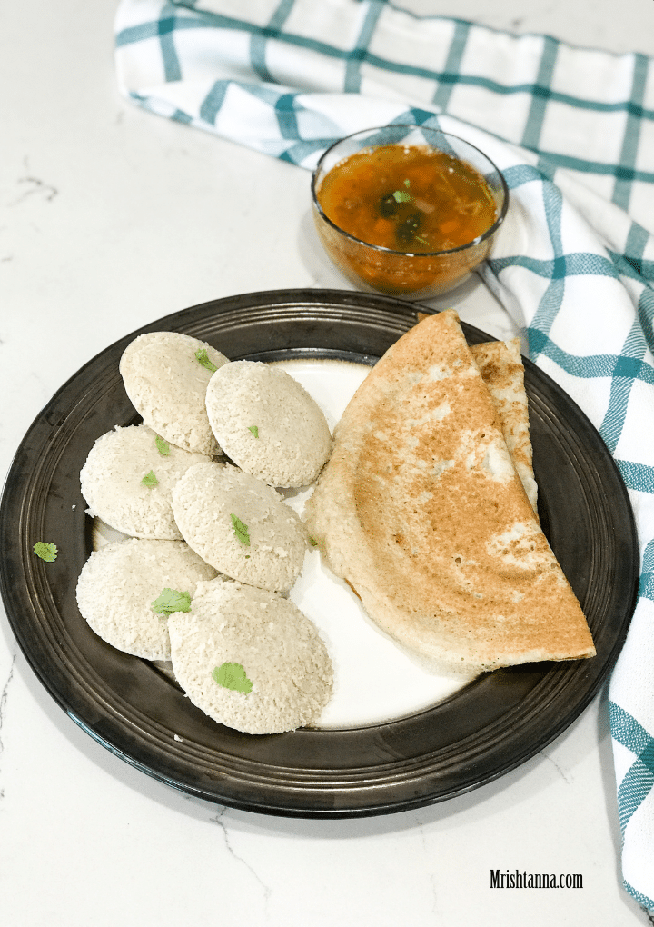 A plate filled with idlis and Millet dosa, along with bowl of sambar