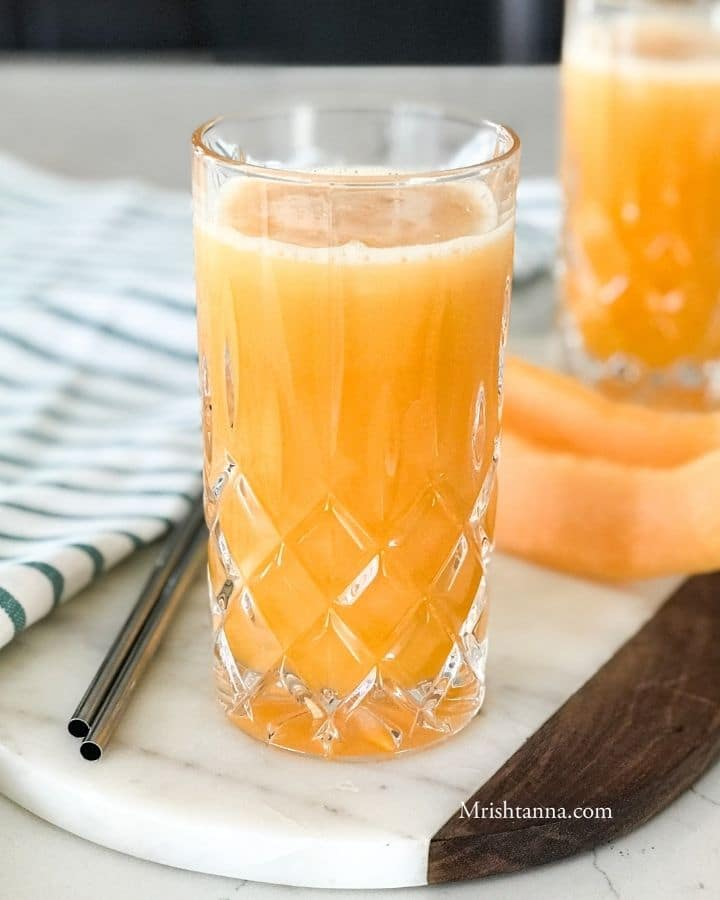 A glass of cantaloupe juice next to a cantaloupe spear