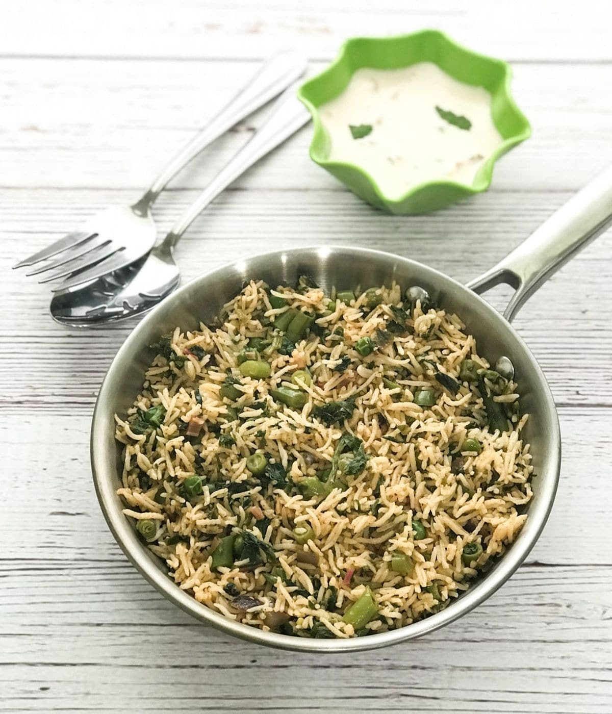 A pan is with spinach rice and bowl of raita on the table
