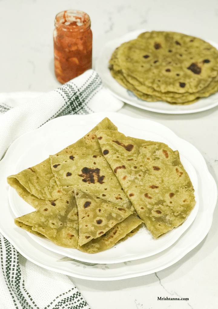 A white plate filled with avocado parathas along with pickle