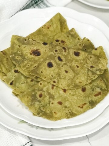 Avocado paratha is placed on a white plate