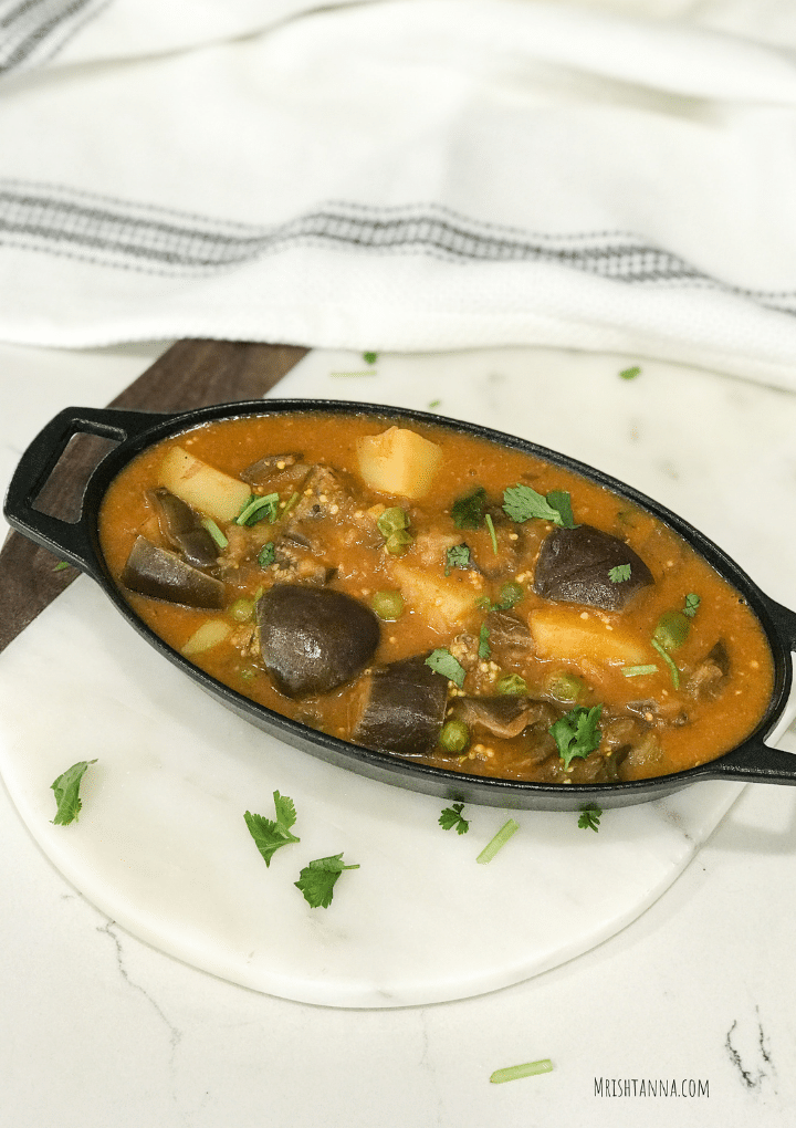 A cast iron bowl filled with eggplant curry