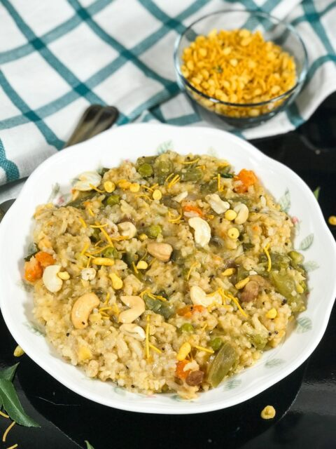 A plate is filled with bisi bele bath and topped with cashews